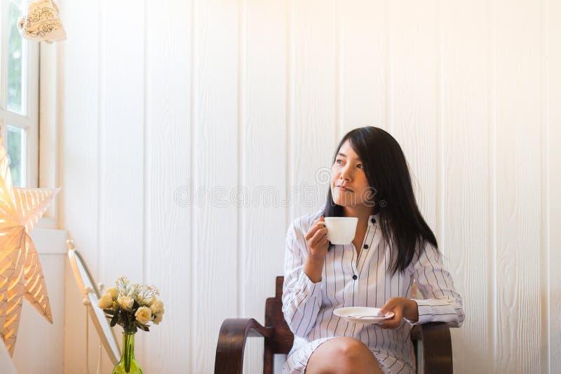 Il ritratto di bella donna asiatica sta tenendo una tazza di tè e sta guardando qualcosa sulla finestra a casa di mattina, felice fotografia stock