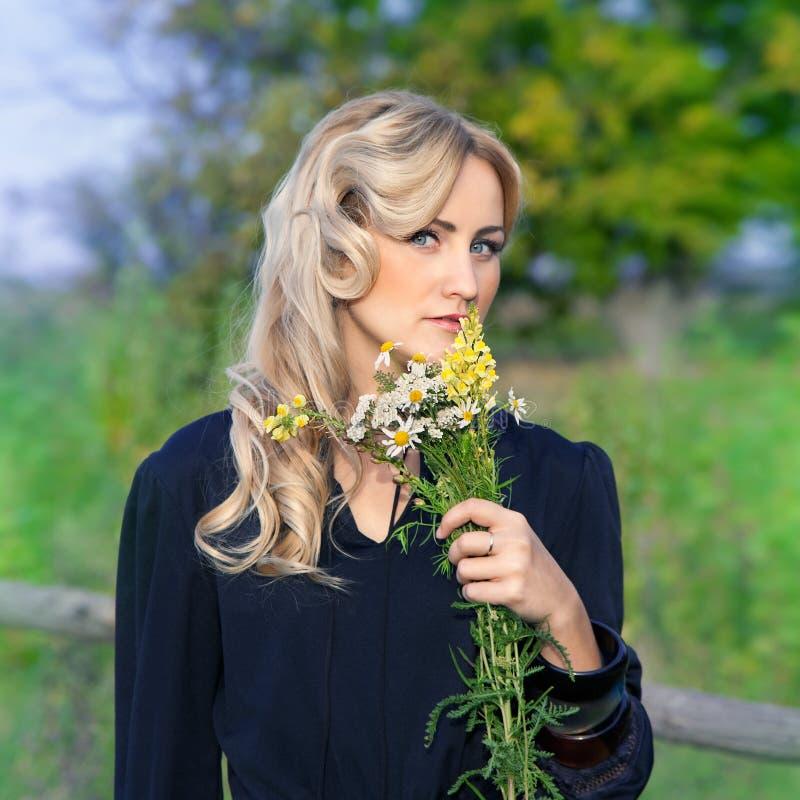 Il ritratto di bella donna bionda con il mazzo fiorisce fotografia stock