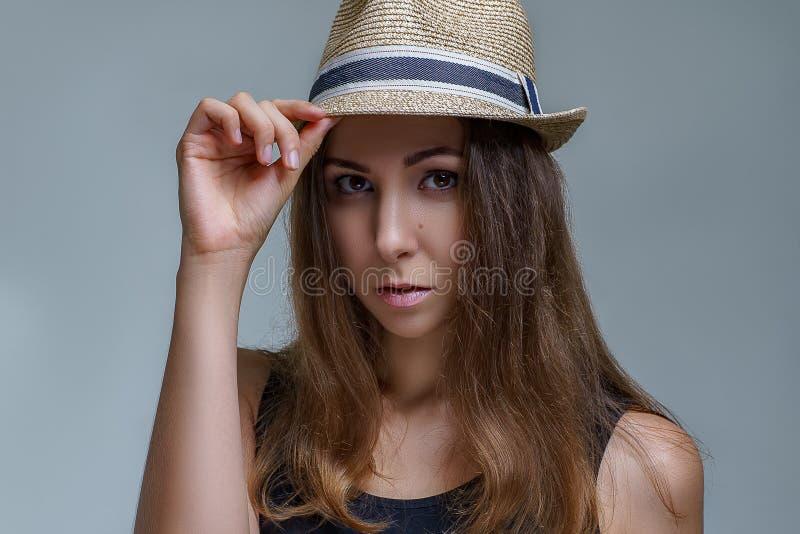 Il ritratto di bella donna castana in un cappello alla moda è posa alla moda sul fondo grigio in una fine dello studio su immagini stock libere da diritti