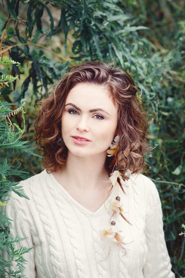 Il ritratto di bella donna caucasica bianca sorridente della ragazza con gli occhi nocciola lunghi dei capelli ricci, in maglione immagine stock