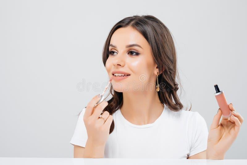 Il ritratto di bella donna che applica il rossetto facendo uso della spazzola di correttore del labbro ha isolato il fondo bianco immagine stock libera da diritti