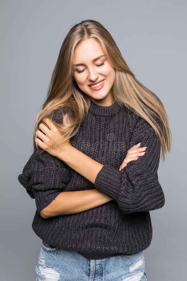 Il ritratto di bella donna che indossa un caldo tricotta il maglione su un fondo grigio isolato immagini stock libere da diritti