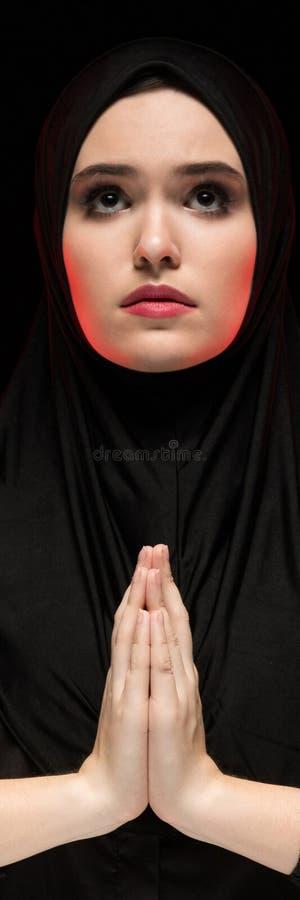 Il ritratto di bella giovane donna musulmana seria che indossa il hijab nero con le mani si avvicina al suo fronte come pregare i immagine stock