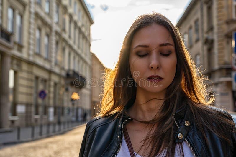 Il ritratto di bella ragazza con gli occhi si è chiuso su una via della città con le vecchie costruzioni con la lampadina del sol immagini stock