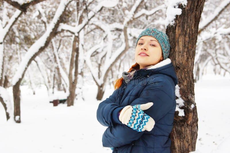 Il ritratto di bella ragazza felice ha peso all'albero nell'inverno fotografia stock