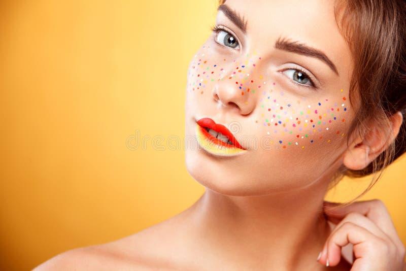 Il ritratto di bella ragazza intelligente con le lentiggini variopinte di arte prepara fotografia stock libera da diritti