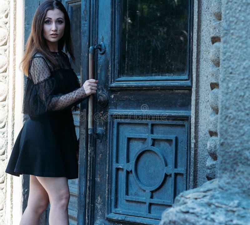 Il ritratto di bella ragazza, una ragazza castana in un vestito nero, supporti vicino ad una grande porta nera, entra in  una nuo fotografie stock libere da diritti