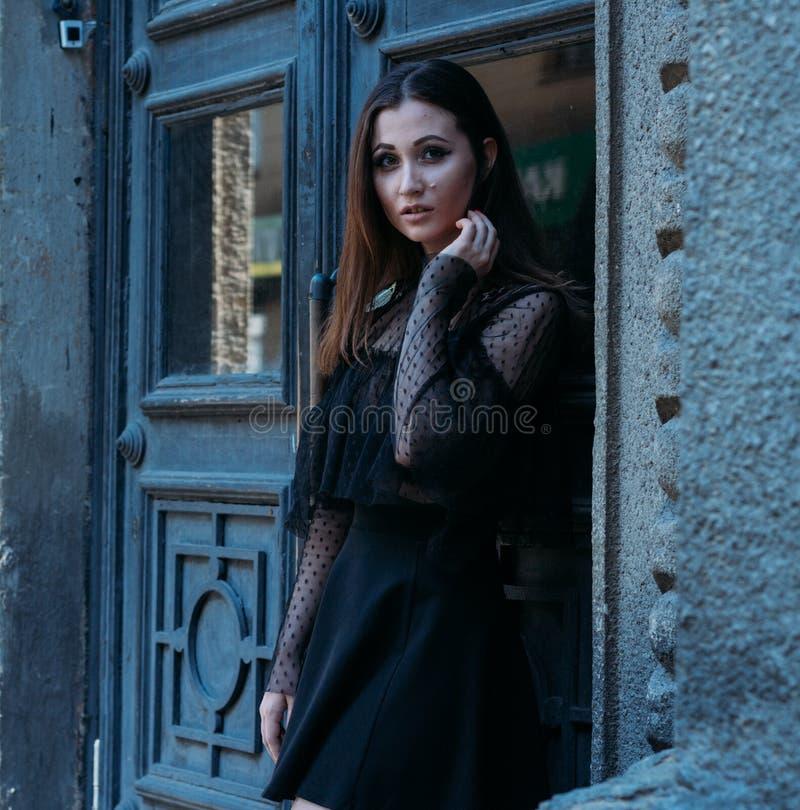 Il ritratto di bella ragazza, una ragazza castana in un vestito nero, supporti vicino ad una grande porta nera, entra in  una nuo fotografie stock