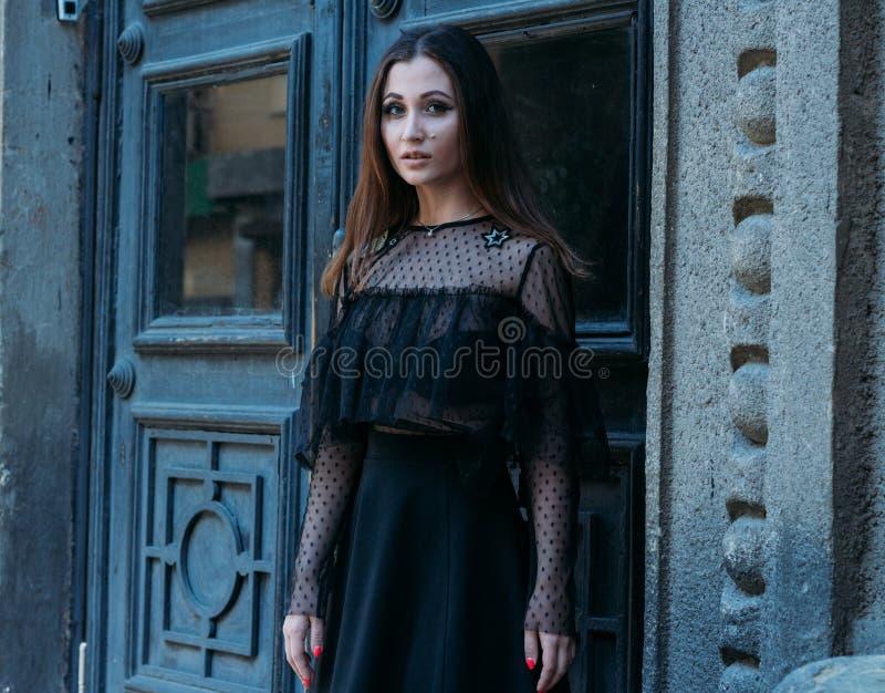 Il ritratto di bella ragazza, una ragazza castana in un vestito nero, supporti vicino ad una grande porta nera, entra in  una nuo fotografia stock libera da diritti