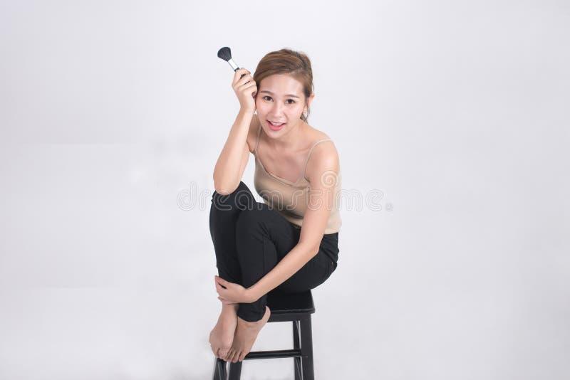 Il ritratto di belle donne asiatiche che tengono la spazzola per compone nella sua mano e nell'esame della macchina fotografica c fotografia stock libera da diritti