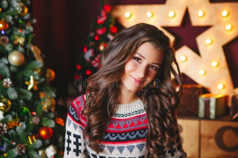 Il ritratto di belle donne ricce sorridenti si avvicina all'albero di Natale celebrazione immagine stock