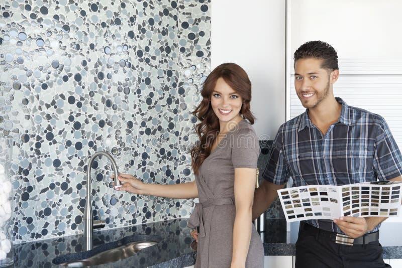 Il ritratto di belle giovani coppie con colore prova la condizione nella cucina della casa di modello immagine stock libera da diritti
