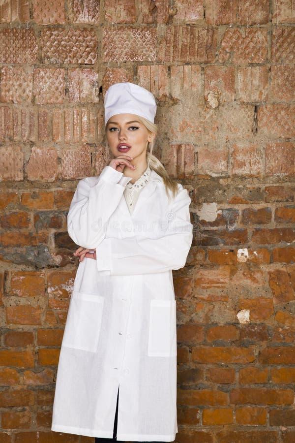 Il ritratto di bello giovane infermiere biondo con le sue armi ha attraversato in un fondo bianco immagini stock libere da diritti