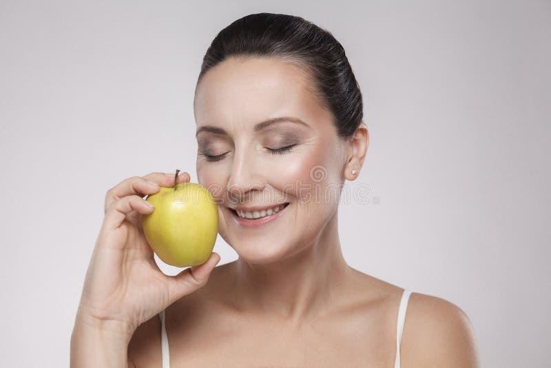 Il ritratto di bello mezzo caucasico sano affascinante ha invecchiato la donna che tiene la mela verde, lei ama mangiare la frutt immagini stock libere da diritti