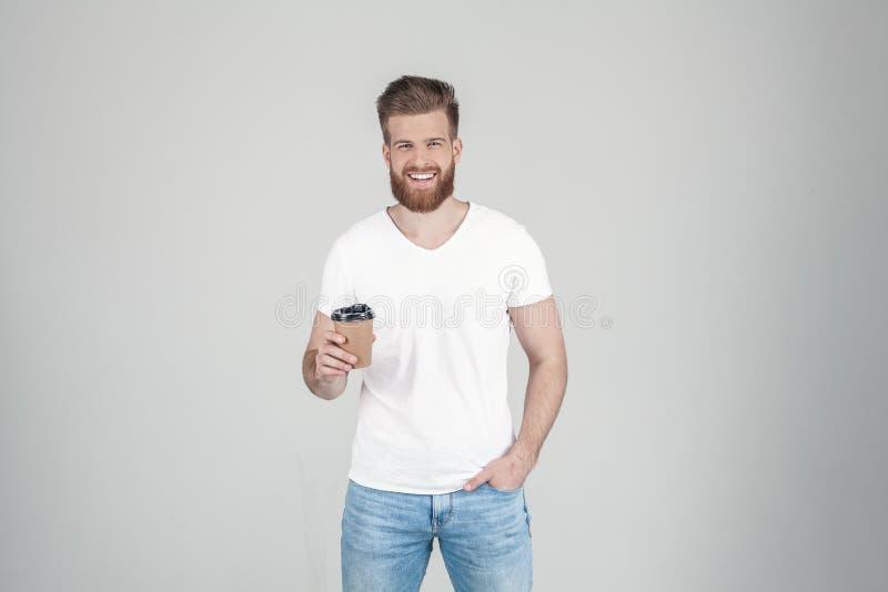 Il ritratto di bello uomo barbuto sexy vestito in una maglietta bianca tiene una tazza di caffè nella suoi mano e sorrisi al immagini stock libere da diritti