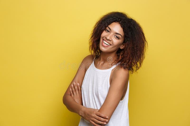 Il ritratto di colpo in testa di bello invio afroamericano attraente della donna ha attraversato le armi con sorridere felice Stu fotografia stock libera da diritti
