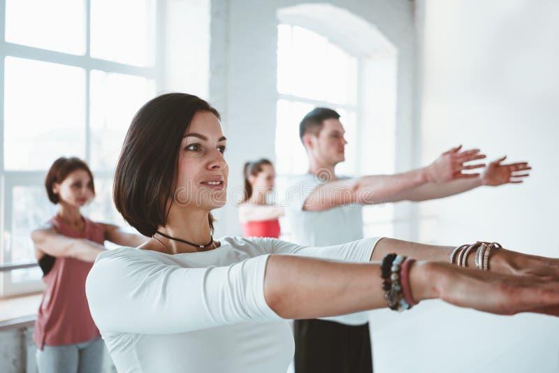 Il ritratto di forte yoga adatta di addestramento della donna posa sulla stuoia di forma fisica insieme al gruppo di persone su f fotografia stock libera da diritti