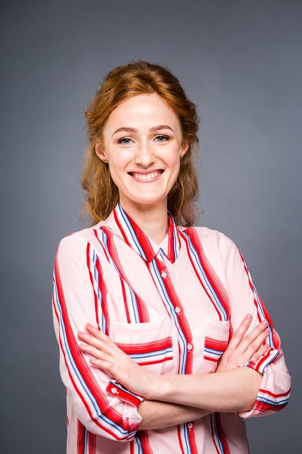 Il ritratto di giovane bella ragazza dai capelli rossi nello studio su un gray ha isolato il fondo Una donna sta e sorride in uno immagine stock libera da diritti