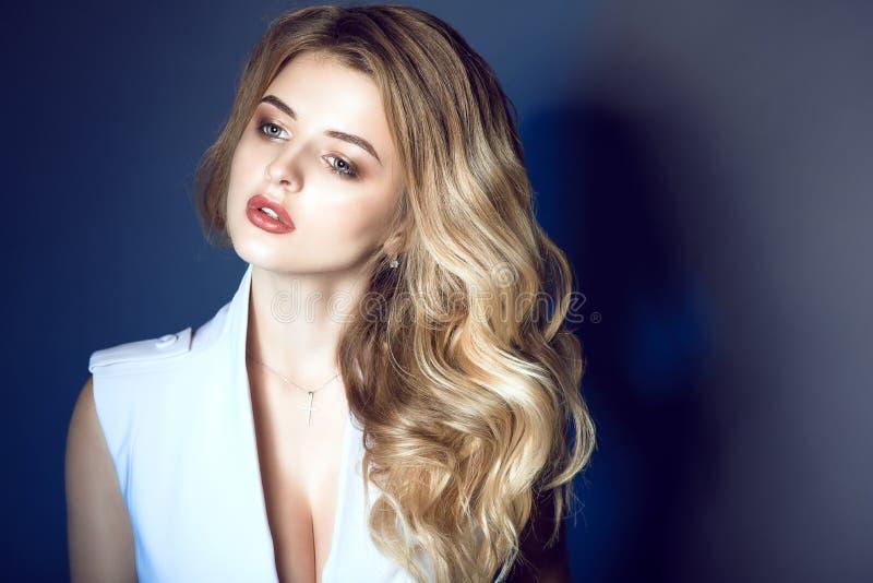Il ritratto di giovane bello modello biondo con capelli ondulati sciccosi e perfetti compongono lo sguardo da parte meditatamente fotografia stock libera da diritti