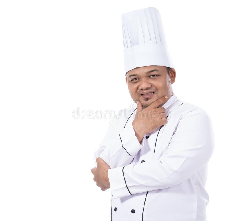 Il ritratto di giovane cuoco unico maschio che sta le mani attraversate sicure posa lo sguardo ad una parte anteriore della macch fotografia stock