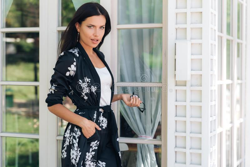Il ritratto di giovane donna attraente sveglia in vestiti di seta e vetri alla moda sta contro il contesto della a fotografie stock libere da diritti