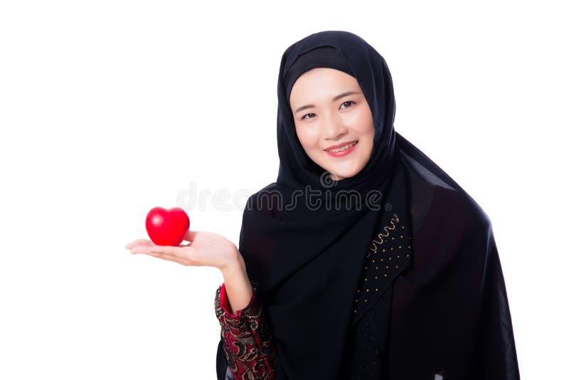 Il ritratto di giovane donna musulmana asiatica che tiene il cuore rosso ha modellato il cuscino fotografie stock