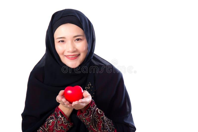 Il ritratto di giovane donna musulmana asiatica che tiene il cuore rosso ha modellato il cuscino isolato immagini stock