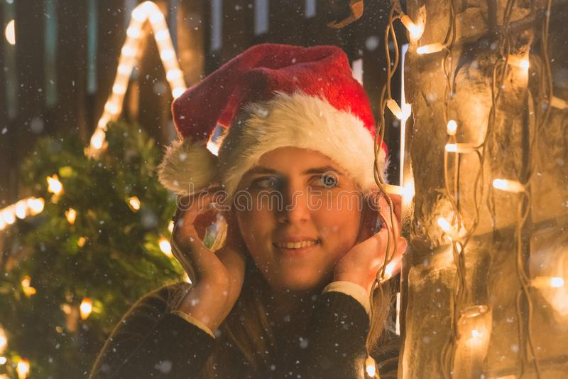 Il ritratto di giovane femmina con la decorazione di Natale si accende all'aperto immagine stock