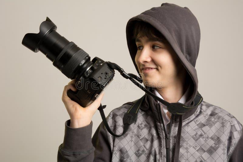 Il ritratto di giovane fotografo allegro con un professionista è venuto fotografia stock libera da diritti