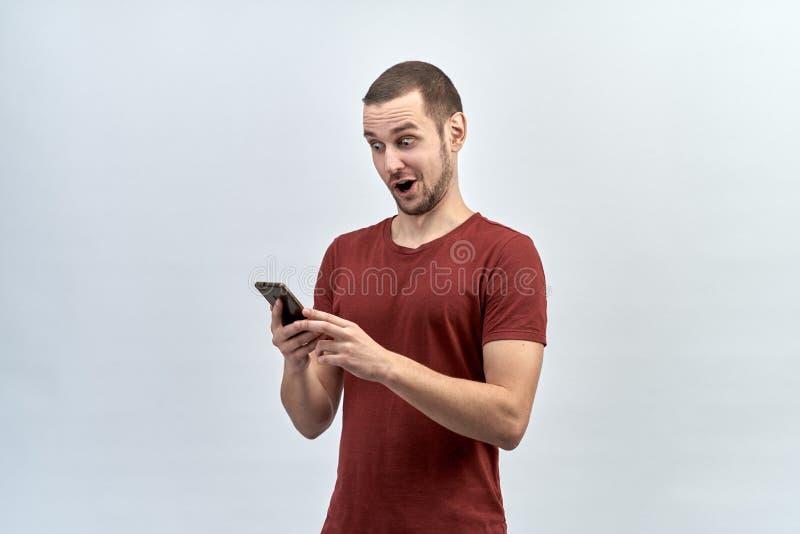 Il ritratto di giovane maschio caucasico che tiene il telefono con due mani con uno sguardo colpito pazzo ed apre la bocca nella  immagine stock
