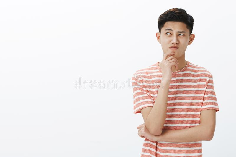 Il ritratto di giovane prova asiatica disturbata del tipo pensa sul piano o sull'idea, stante nella posa premurosa con la mano su fotografia stock