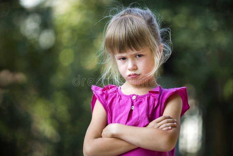 Il ritratto di giovane ragazza bionda lunatica divertente graziosa del bambino in vestito senza maniche rosa guarda in camera rit fotografia stock libera da diritti