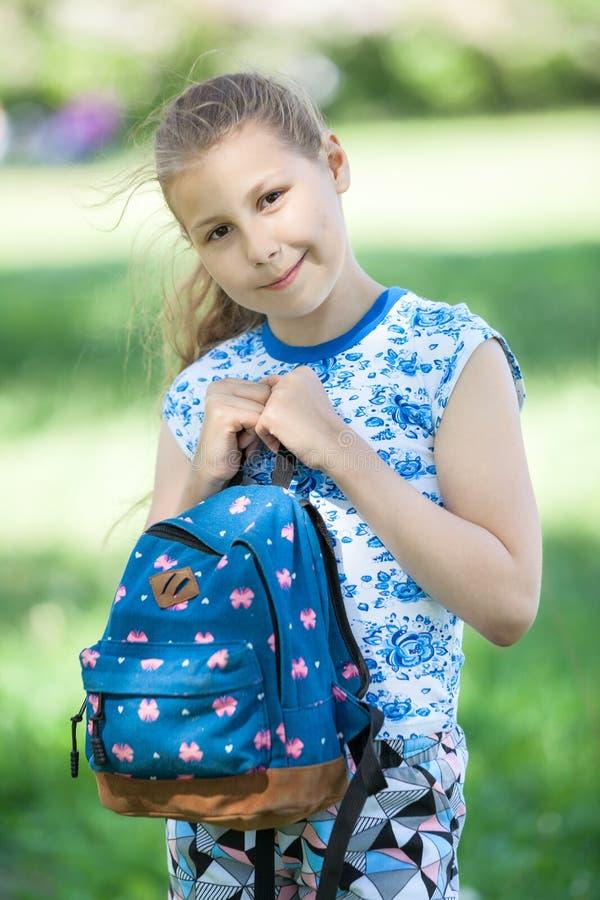 Il ritratto di giovane ragazza graziosa stringe a sé la borsa al corpo, stante nel parco dell'estate fotografie stock libere da diritti