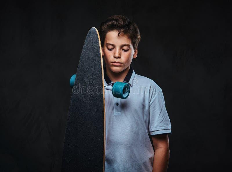 Il ritratto di giovane ragazzo del pattinatore ha vestito nelle tenute bianche di una maglietta un longboard Sui precedenti scuri fotografia stock