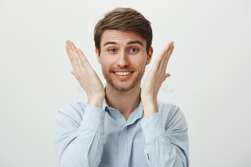 Il ritratto di giovane sensibilità bella dell'imprenditore alleviata e felice, alzando le palme si avvicina al fronte, al sorride fotografia stock