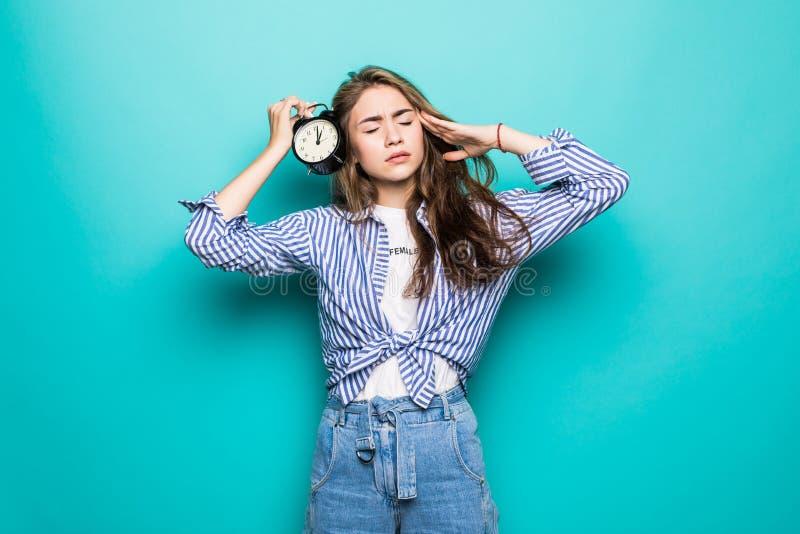 Il ritratto di giovane studentessa imbarazzata turbata in vestiti del denim giudica la sveglia isolata su fondo blu Il tempo sta  fotografie stock