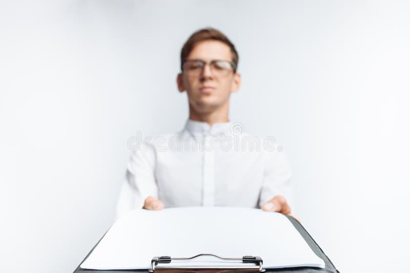 Il ritratto di giovane tipo in vetri, in una camicia bianca, mostra una cartella vuota sulla macchina fotografica, isolata su un  fotografie stock libere da diritti