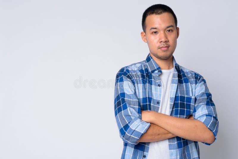 Il ritratto di giovane uomo asiatico dei pantaloni a vita bassa con le armi ha attraversato fotografia stock libera da diritti