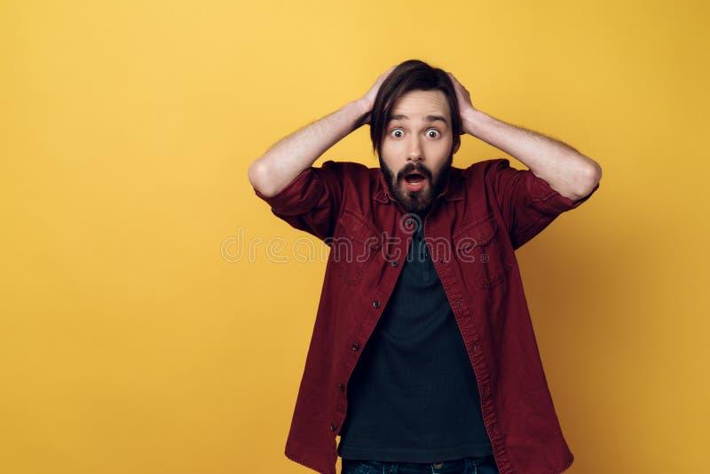 Il ritratto di giovane uomo barbuto interessato tiene la testa fotografia stock libera da diritti
