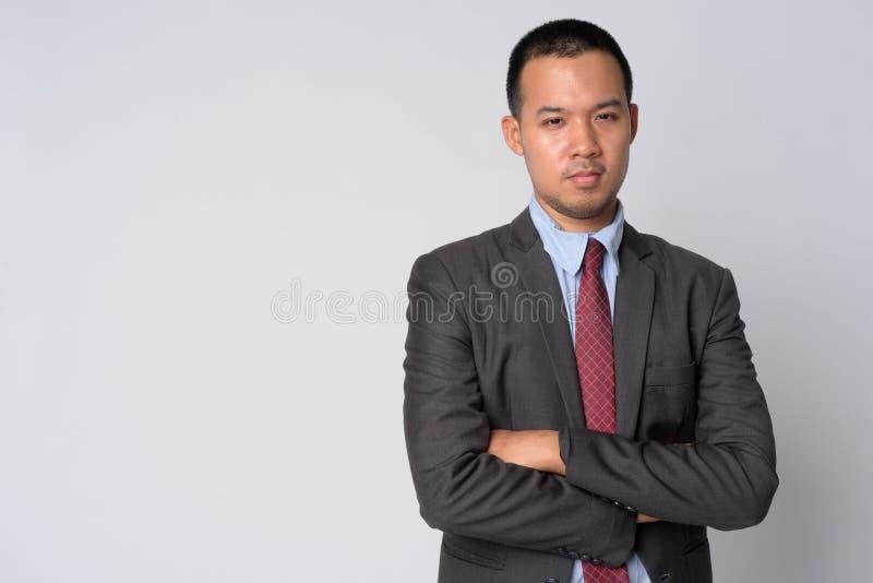 Il ritratto di giovane uomo d'affari asiatico in vestito con le armi ha attraversato fotografia stock libera da diritti