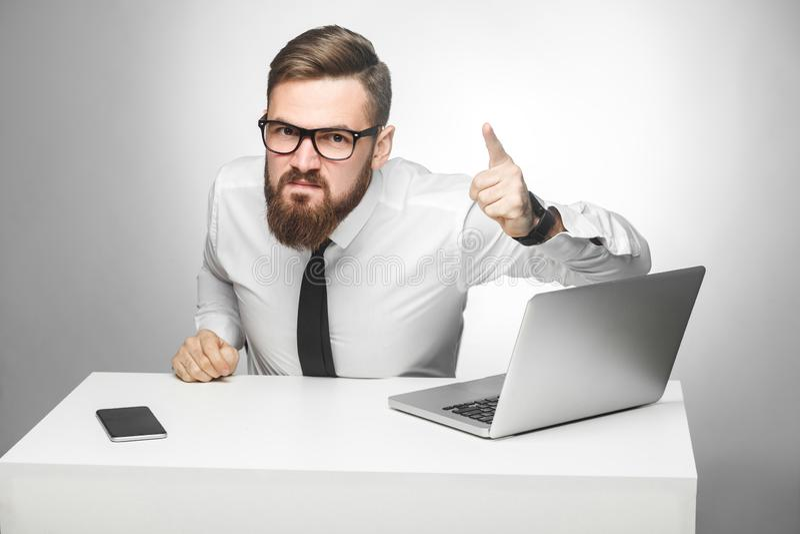 Il ritratto di giovane uomo d'affari infelice aggressivo in camicia bianca e lo smoking stanno incolpandovi in ufficio e stanno a fotografia stock