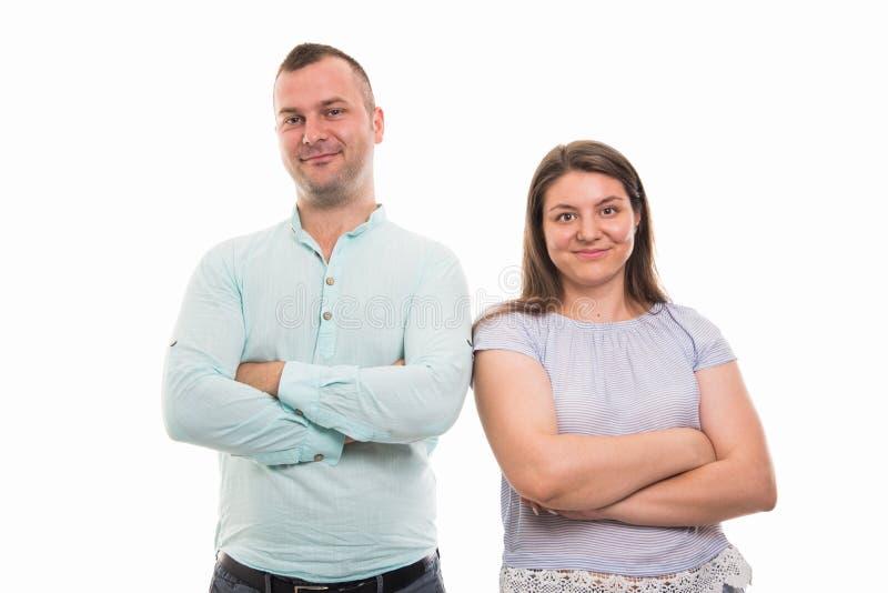 Il ritratto di giovani coppie felici che stanno con le armi ha attraversato il gestur fotografia stock