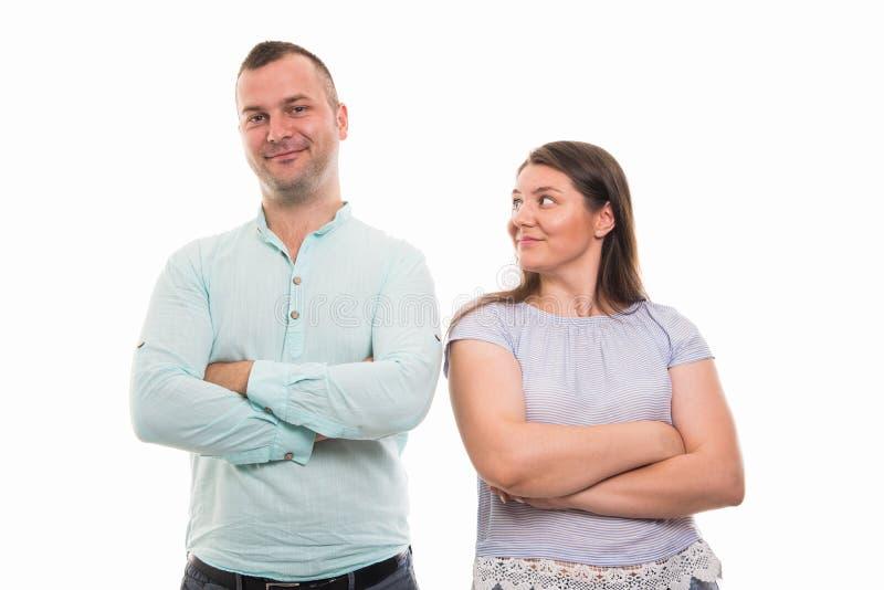 Il ritratto di giovani coppie felici che stanno con le armi ha attraversato il gestur immagini stock