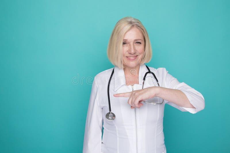 Il ritratto di medico femminile che indica qualcosa ha isolato nello studio blu fotografia stock