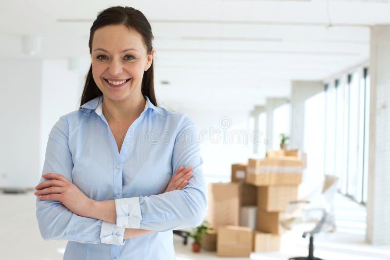 Il ritratto di metà di armi adulte sorridenti di condizione della donna di affari ha attraversato in nuovo ufficio immagine stock