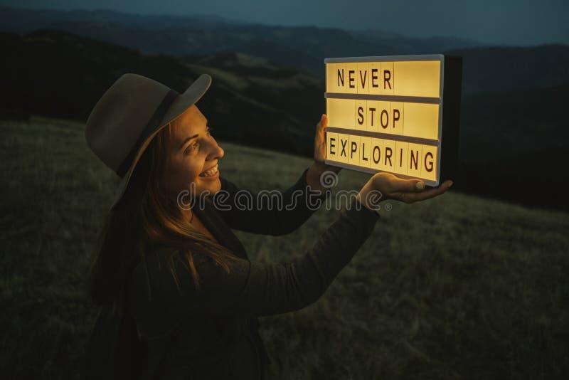 Il ritratto di notte della donna in cappello con la scatola con testo non ferma mai la e fotografia stock libera da diritti
