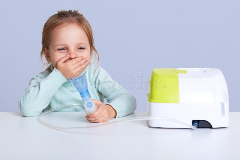 Il ritratto di piccola ragazza che fa l'inalazione, sedentesi alla tavola, dura in maglione blu-chiaro del collo del turle, ha pr immagini stock