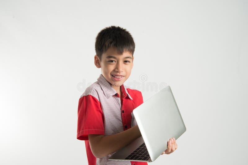 Il ritratto di poco ragazzo della miscela prende una compressa del taccuino sopra fotografia stock