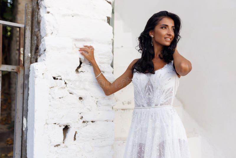 Il ritratto di profilo di una sposa in un vestito da sposa bianco, toccante leggermente i suoi capelli, posa vicino ad una parete fotografie stock libere da diritti