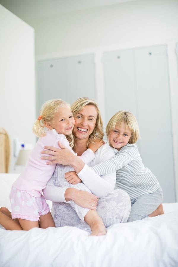 Il ritratto di sorridere scherza l'abbraccio di sua madre in camera da letto fotografie stock libere da diritti